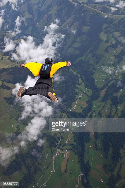 Skydiver with wings is flying high over clouds.