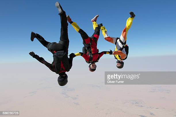 Skydivers holding hands and having fun