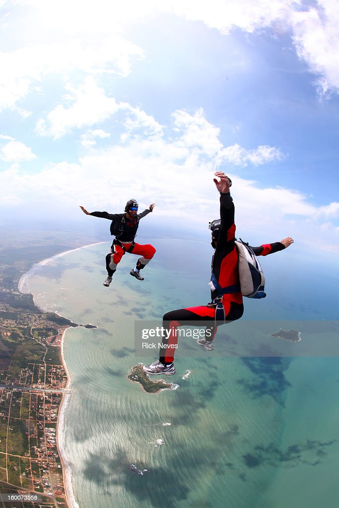 Skydivers in freefall over the beach : Stock Photo