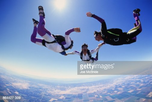 Skydivers linked in free fall formation, low angle view [1995] : Stock Photo