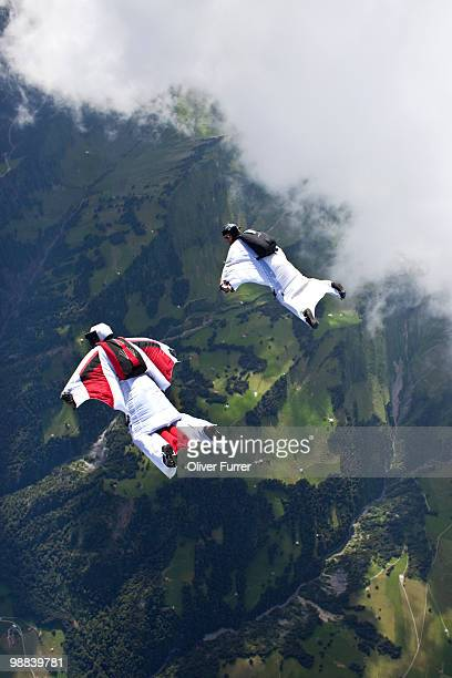 Skydivers with wings flying high over clouds.