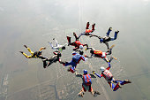A group of paratroopers construct figures in free fall.
