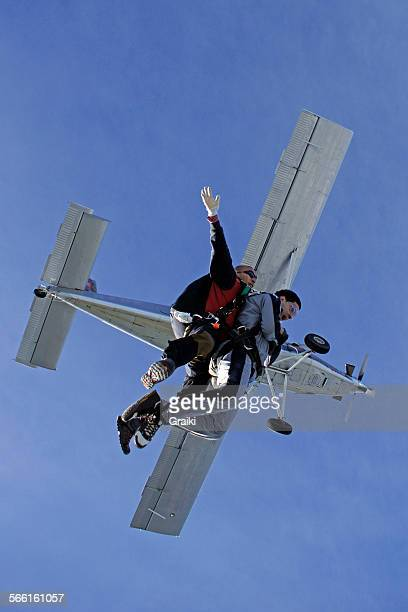 Skydiving tandem exit from a grey plane