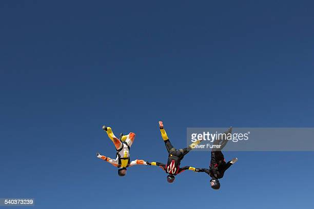 Skydiving team holding hands together in the sky