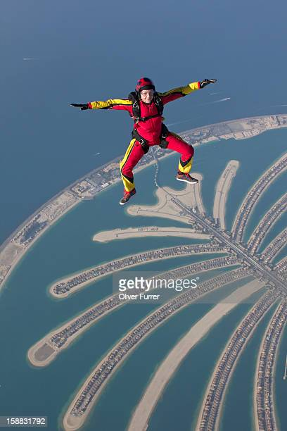 Skydiving woman free flying over Dubai palm