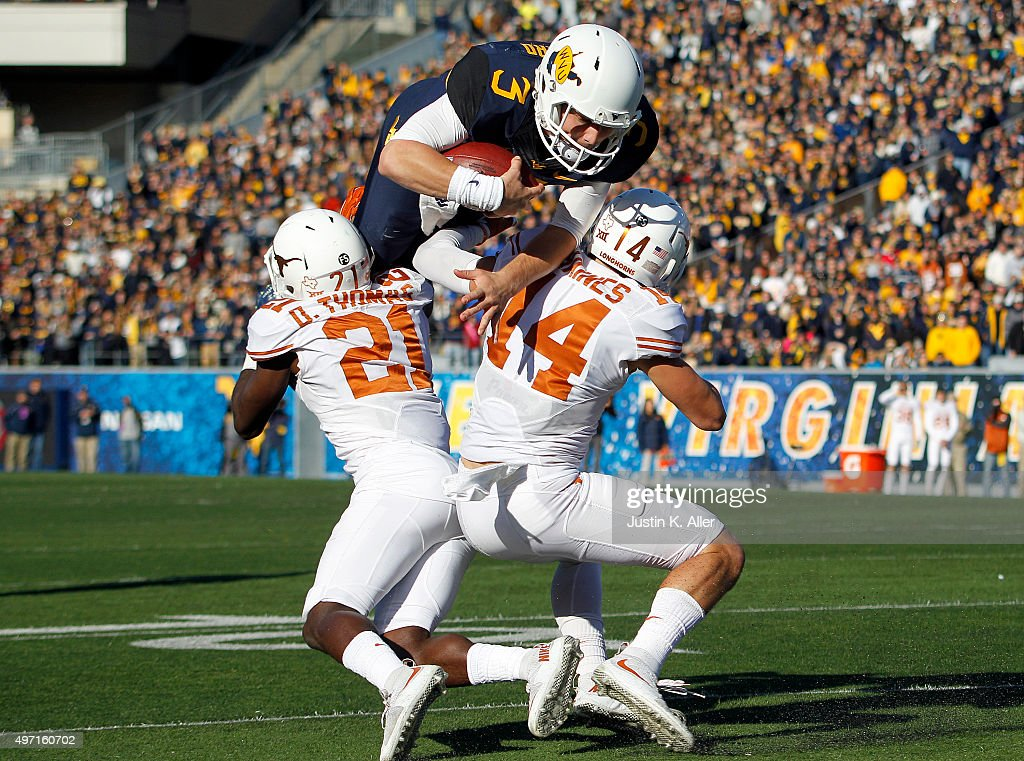 Skyler Howard of the West Virginia Mountaineers attempts to hurdle Duke Thomas and Dylan Haines of the Texas Longhorns in the second half during the...