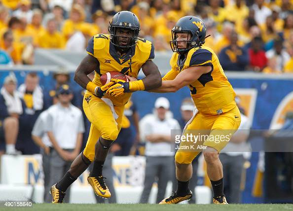 Skyler Howard of the West Virginia Mountaineers hands off to Wendell Smallwood in the second quarter during the game against the Maryland Terrapins...