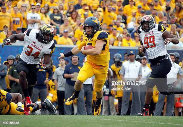 Skyler Howard of the West Virginia Mountaineers rushes against Quinton Jefferson and Jefferson Ashiru of the Maryland Terrapins during the game on...