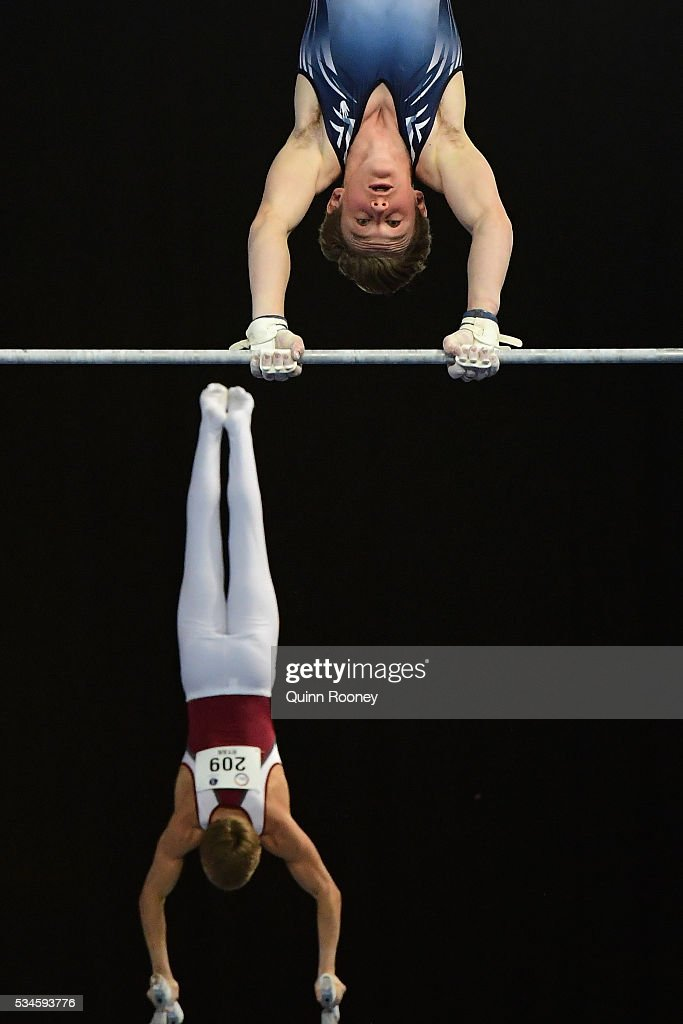 Skyler Kah of Victoria competes on the high bar as Joseph Ryan of Queensland competes on the parrallel bars during the 2016 Australian Gymnastics Championships at Hisense Arena on May 27, 2016 in Melbourne, Australia.
