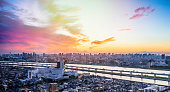 Business and culture concept - panoramic modern city skyline bird eye aerial view with Mountain Fuji under dramatic sunset glow and beautiful cloudy sky in Tokyo, Japan