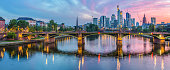 Beautiful cityscape Panorama of Frankfurt at Main. Illuminated bridge in the foreground and the financial skyscraper district in the background.