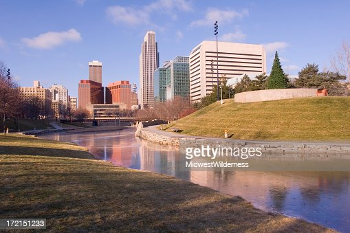 Skyline of city behind public park with water