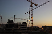 Construction of new homes. Silhouettes of cranes on the background of the evening sky.