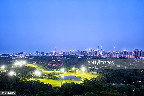 skyline of modern city with golf course at night