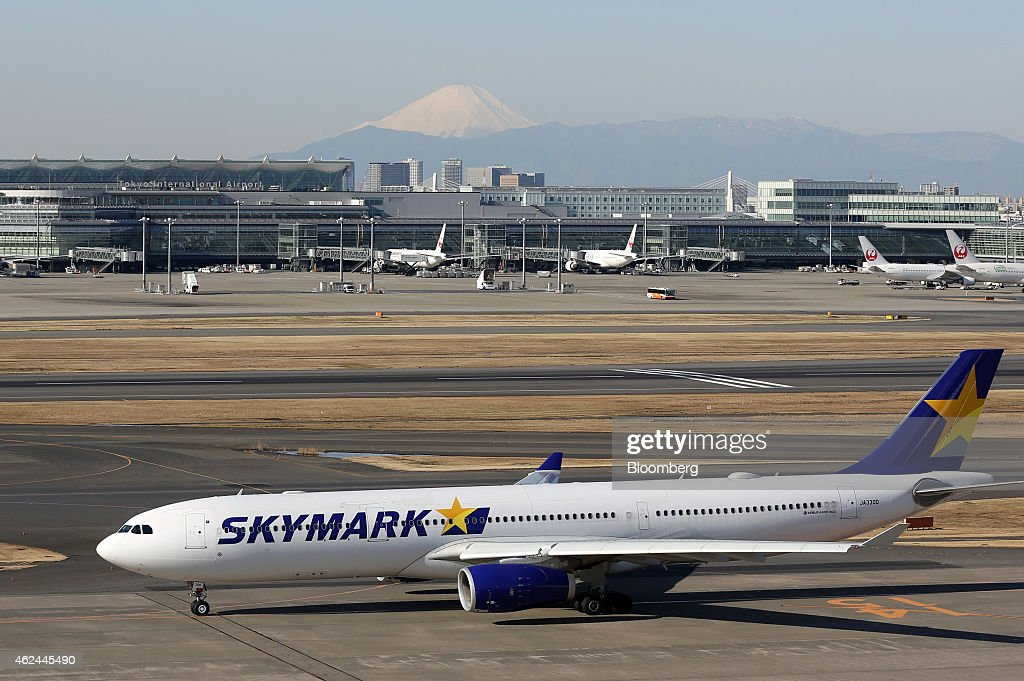 A Skymark Airlines Inc aircraft taxies against a backdrop of Mount Fuji at Haneda Airport in Tokyo Japan on Thursday Jan 29 2015 Skymark Japan's...