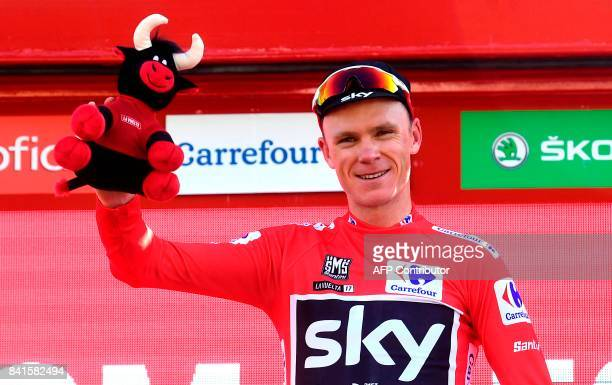 Sky's British cyclist Christopher Froome celebrates on the podium wearing the leader's red jersey after the 13th stage of the 72nd edition of 'La...
