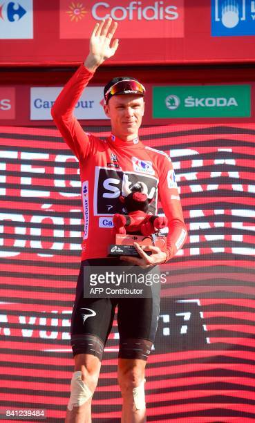 Sky's British cyclist Christopher Froome sports the leader's red jersey as he waves on the podium of the 12th stage of the 72nd edition of 'La...