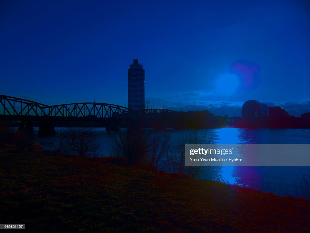 Skyscraper By Bridge Over River Against Blue Sky At Night : Stock-Foto