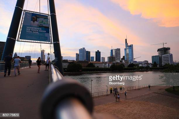 Skyscrapers stand beyond the River Main as pedestrians walk neaerby in Frankfurt Germany on Wednesday July 19 2017 Frankfurt has emerged as a winner...