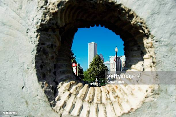 Skyscrapers viewed through a hole in a wall, Gateway Park, Chicago, Illinois, USA