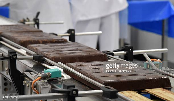Slabs of chocolate bars are moved along a conveyer belt following the inauguration of the French chocolate manufacturers CEMOI factory in Abidjan on...