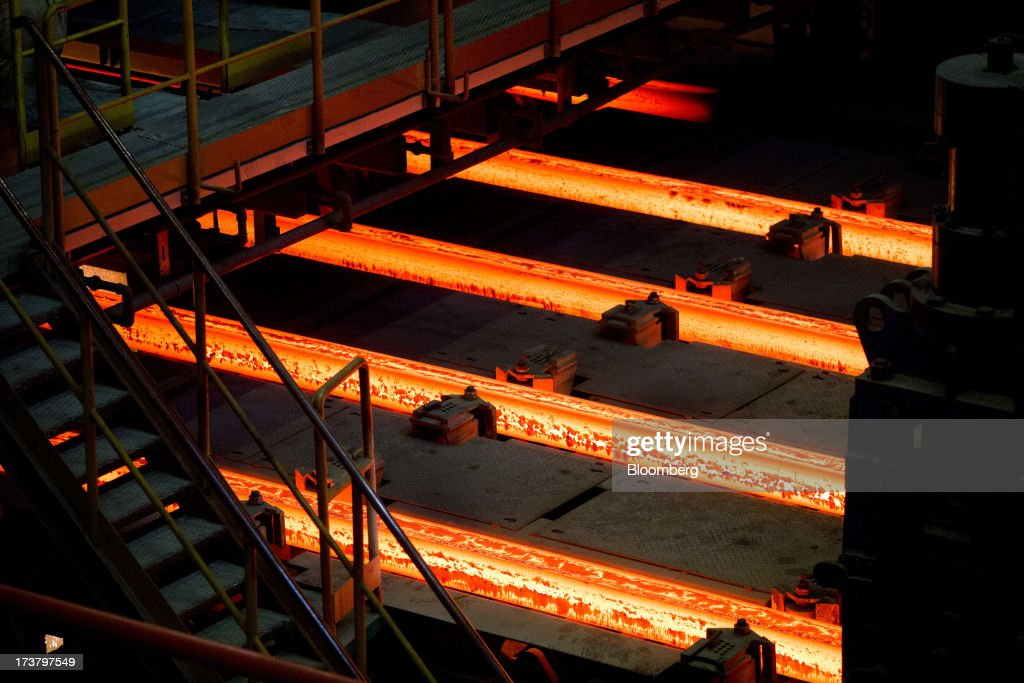 Slabs of red hot steel pass along the production line at OAO Mechel's metallurgical plant in Chelyabinsk, Russia, on Wednesday, July 17, 2013. Mechel, the country's largest producer of coking coal for steelmakers has begun operating its $700m rail production line which can produce 100 meter rails. Photographer: Andrey Rudakov/Bloomberg via Getty Images