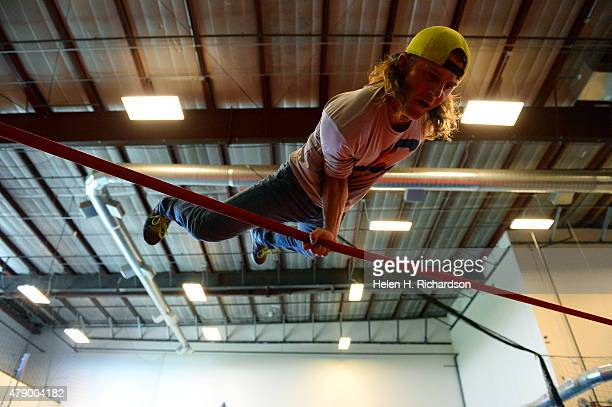 Slackline champion Mickey Wilson practices a one arm lever on a slack line at Progresh an action sports facility in Thornton Colorado on June 29 2015...