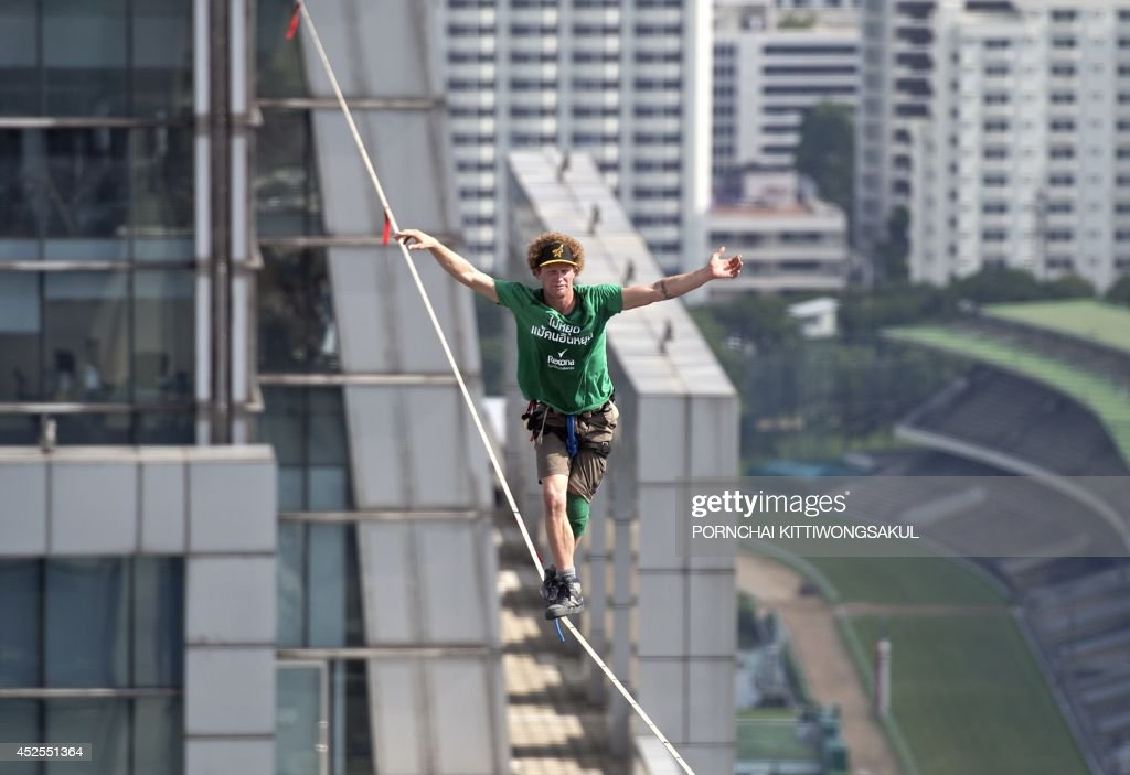 Slackliner, Andy Lewis of the US balances as he walks on a highline from the rooftop of a building in Bangkok on July 23, 2014. Lewis set a world record after walking on a highline from the rooftop of a building to another covering a distance of 169 metres in one hour and five minutes.