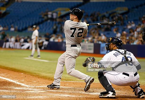 Slade Heathcott of the New York Yankees hits a threerun home run in front of catcher JP Arencibia of the Tampa Bay Rays during the ninth inning of a...