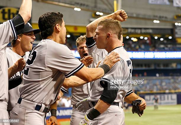 Slade Heathcott of the New York Yankees is surrounded by teammates including Jacoby Ellsbury after hitting a threerun home run during the ninth...