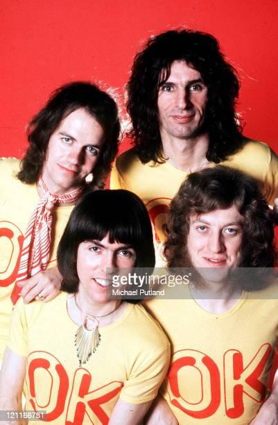 Slade studio group portrait London wearing tshirts with the slogan 'OK' LR Jim Lea Dave Hill Don Powell Noddy Holder