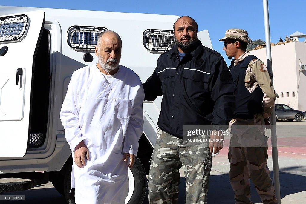 Slain Libyan leader Moamer Kadhafi's last premier Al-Baghdadi al-Mahmudi (L) arrives to attend his trial at a courtroom in Tripoli on February 11, 2013. Al-Mahmudi is accused of killing civilians and financial crimes.