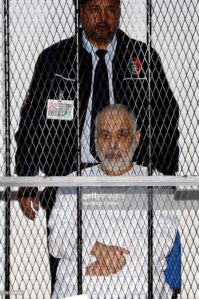 Slain Libyan leader Moamer Kadhafi's last premier Al-Baghdadi al-Mahmudi (L) sits inside the accused cage as he attends his trial at a courtroom in Tripoli on February 11, 2013. Al-Mahmudi is accused of killing civilians and financial crimes.