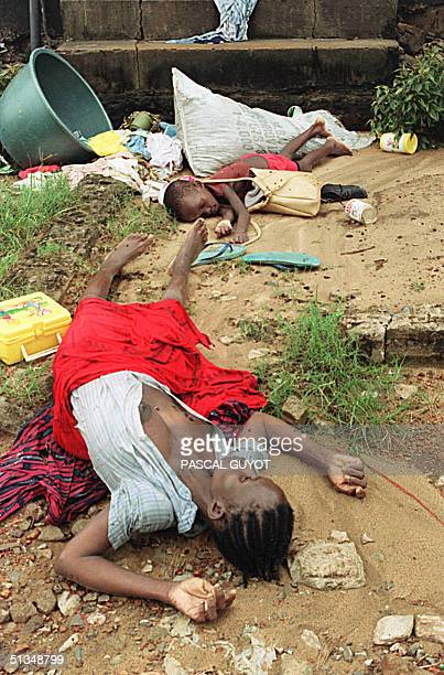 A slain woman and her child lie on the ground afer they were killed 20 August 1990 during fighting in Monrovia between rebel forces of the National...