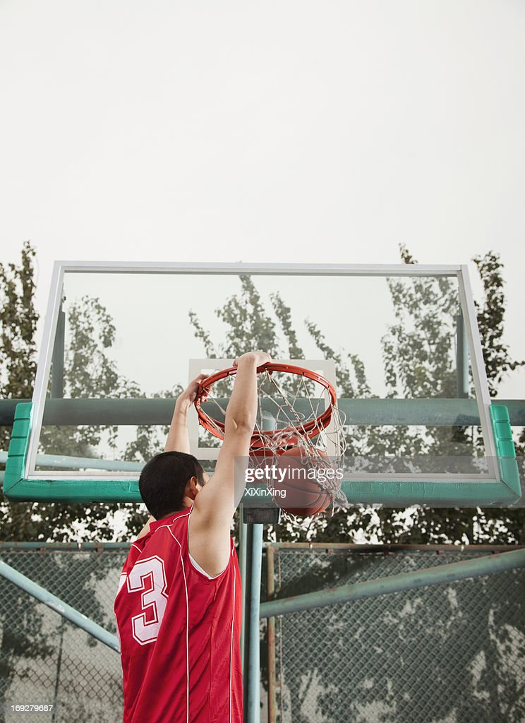 Slam dunk by young man : Stock Photo