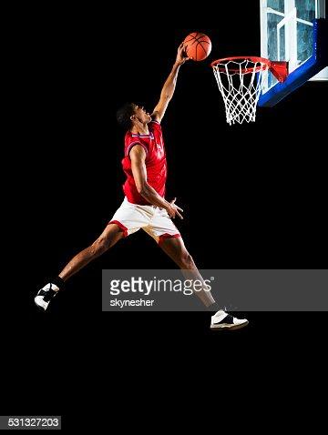 Slam dunking the ball.