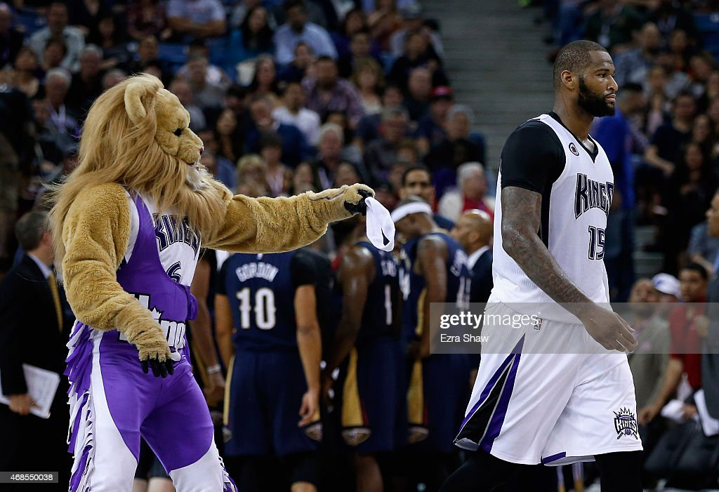 Slamson the Lion, the Sacramento Kings mascot, tries to give DeMarcus Cousins #15 back his head band after it fell off during their game against the New Orleans Pelicans at Sleep Train Arena on April 3, 2015 in Sacramento, California.