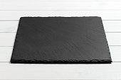 Slate blackboard on wooden table on wooden background.