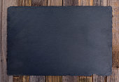 Black slate board over wooden background