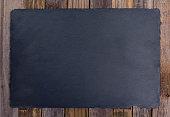 Black slate board over wooden background
