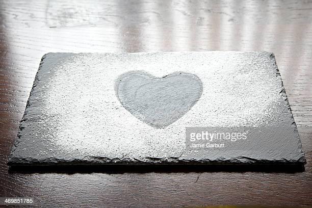 Slate with a icing sugar heart shape