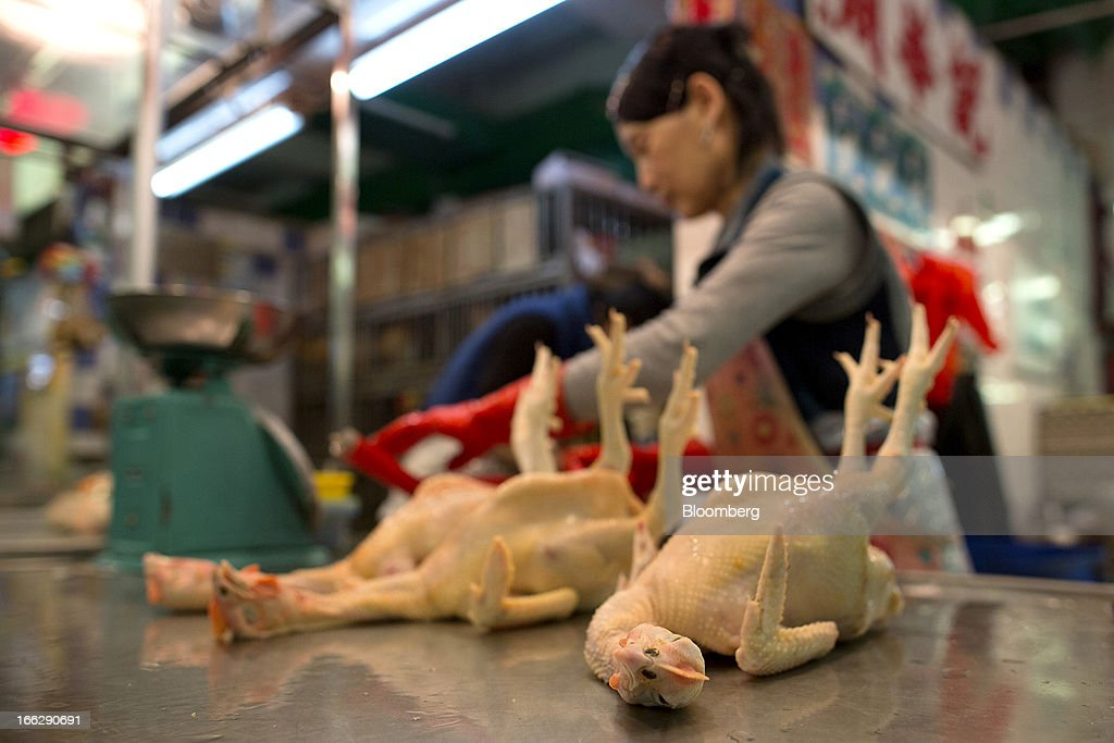 Slaughtered chickens lie on a counter as a vendor works in the background at the Kowloon City Market in Hong Kong, China, on Thursday, April 11, 2013. The Hang Seng Index rose 0.8 percent to 22,220.65 as of 1:14 p.m. in Hong Kong, headed for its longest winning streak since March 27. The gauge is close to erasing last week's loss prompted by the outbreak of a new strain of bird flu in China. Photographer: Jerome Favre/Bloomberg via Getty Images