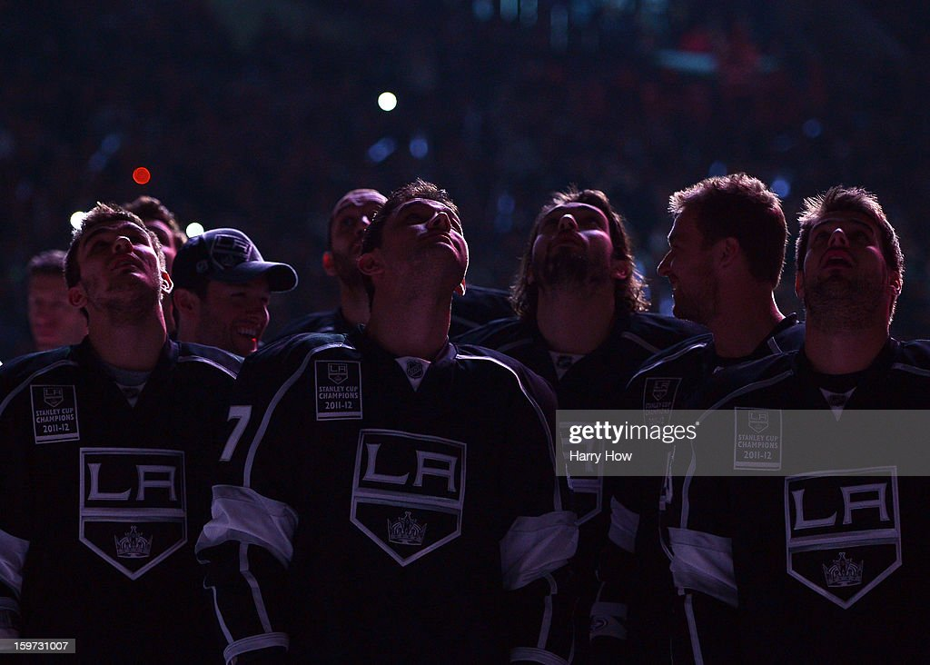 Slava Voynov #26, Alec Martinez #27 Drew Doughty #8, Jeff Carter #77 and Brad Richardson #15 of the Los Angeles Kings watch as the 2001-12 Stanley Cup banner is raised during a ceremony before the NHL season opening game against the Chicago Blackhawks at Staples Center on January 19, 2013 in Los Angeles, California.