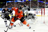 Slava Voynov and Jeff Carter of the Los Angeles Kings pressure Saku Koivu of the Anaheim Ducks during the 2014 Coors Light NHL Stadium Series game...