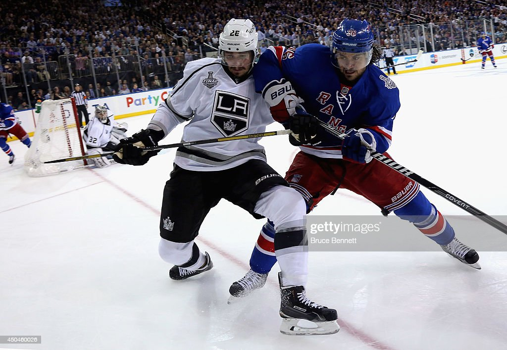 Slava Voynov #26 of the Los Angeles Kings and Mats Zuccarello #36 of the New York Rangers battle for the puck during the second period of Game Four of the 2014 NHL Stanley Cup Final at Madison Square Garden on June 11, 2014 in New York, New York.