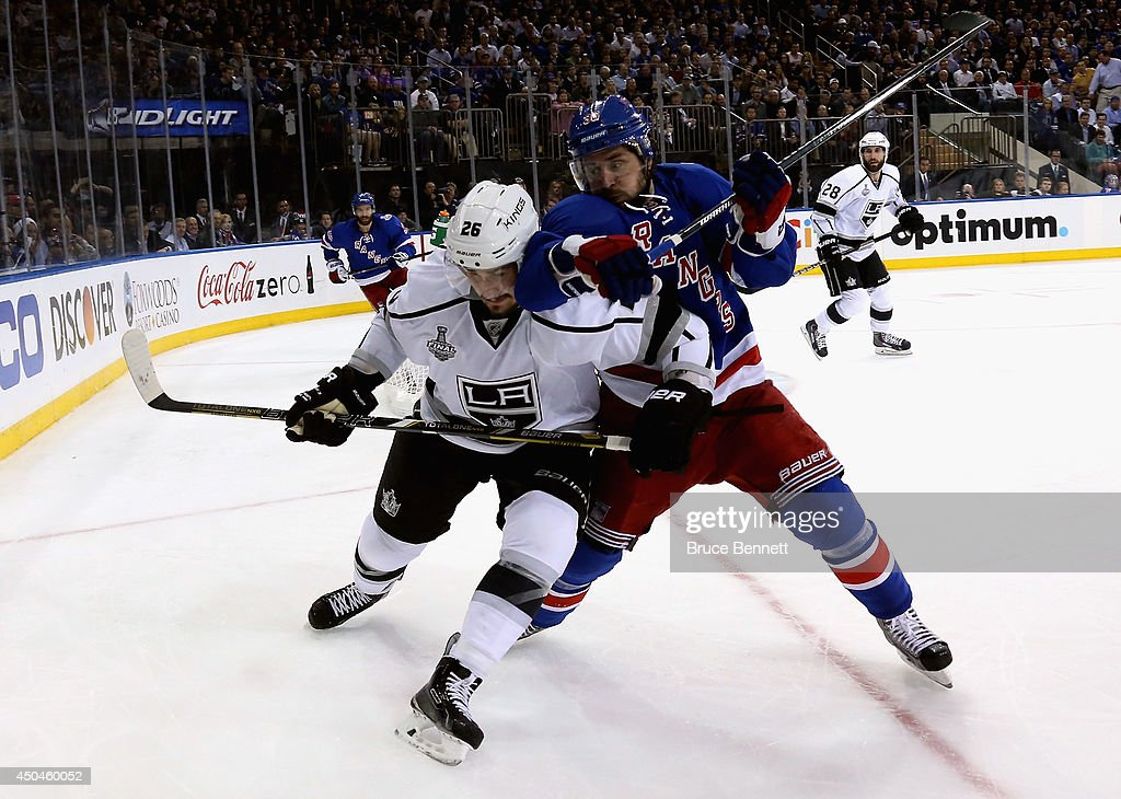 Slava Voynov #26 of the Los Angeles Kings and Mats Zuccarello #36 of the New York Rangers battle for the puck during the first period of Game Four of the 2014 NHL Stanley Cup Final at Madison Square Garden on June 11, 2014 in New York, New York.