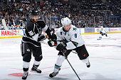 Slava Voynov of the Los Angeles Kings battles for the puck against Joe Pavelski of the San Jose Sharks during the NHL season opener at STAPLES Center...