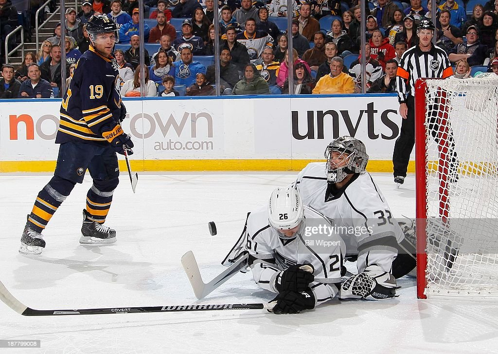 Slava Voynov #26 of the Los Angeles Kings blocks a shot headed toward the net guarded by Kings' goaltender Jonathan Quick #32 as Cody Hodgson #19 of the Buffalo Sabres watches on November 12, 2013 at the First Niagara Center in Buffalo, New York.