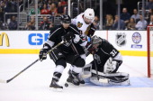 Slava Voynov of the Los Angeles Kings defends the play to the net by Patrick Sharp of the Chicago Blackhawks as goaltender Jonathan Quick of the Los...