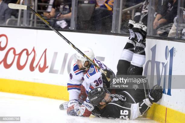 Slava Voynov of the Los Angeles Kings falls into the boards alongside Mats Zuccarello of the New York Rangers in overtime during Game Five of the...